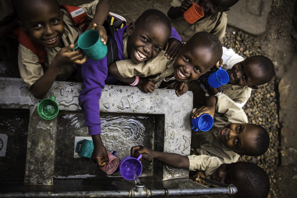 Children fill their cups at a water point built by UNICEF at Kanyosha III primary school in Bujumbura.